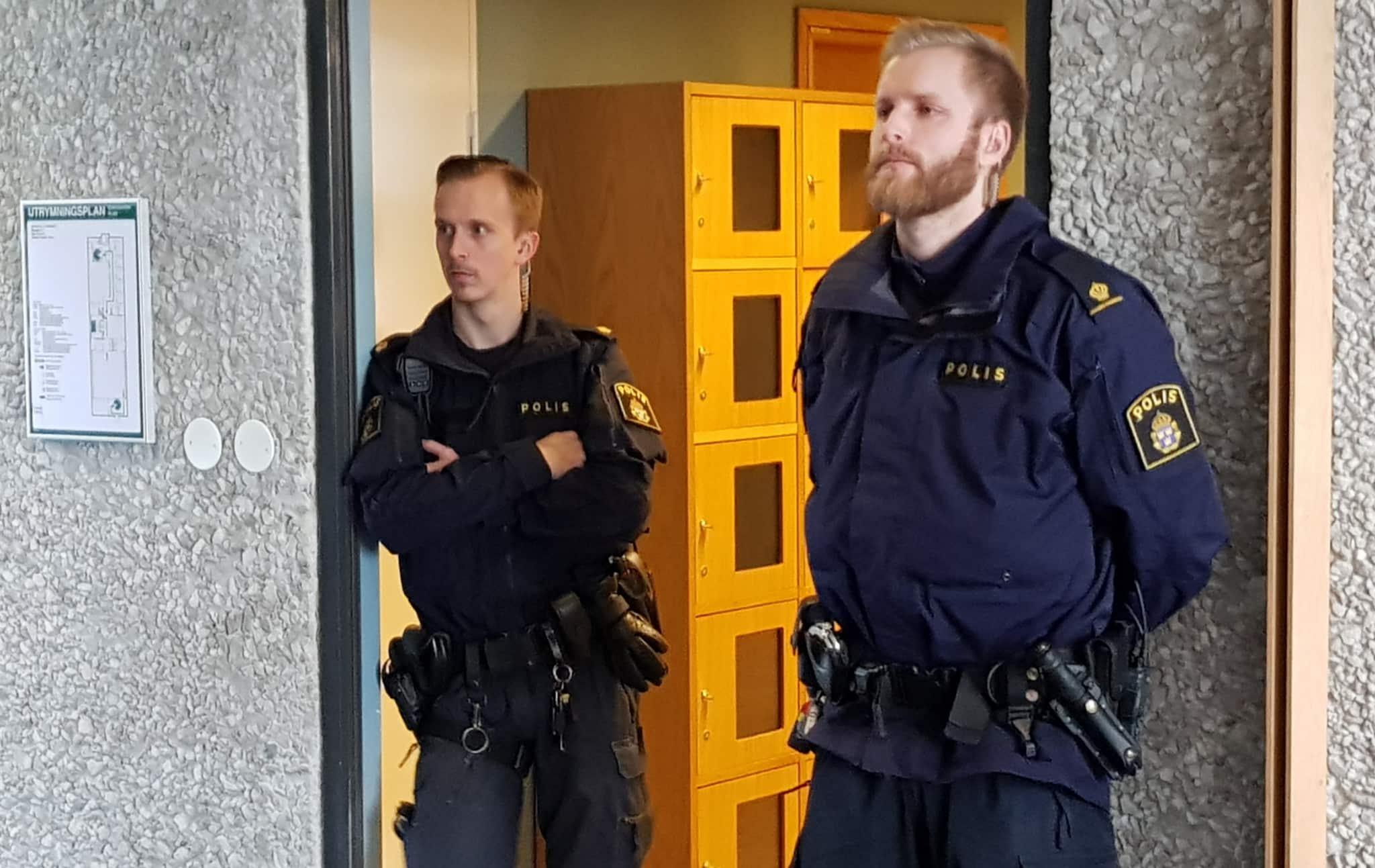 Av någon anledning bevakas rättegången mot vargskytten inte bara av ordinarie väktare utan också av polis.