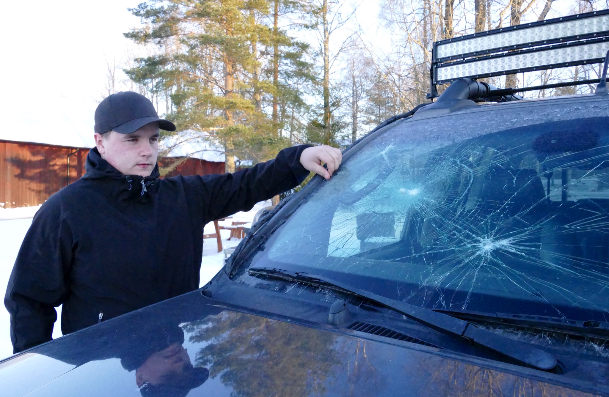 Mattias Heed med sin bil som någon eller några slagit sönder efter att han avlivat en trafikskadad varg. Foto: Boo Westlund