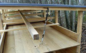 Genom att fästa ett par karbinhakar i taket kan luckorna enkelt hängas upp när fällan ska betas och gillras om efter fångst. Foto: Bernt Karlsson