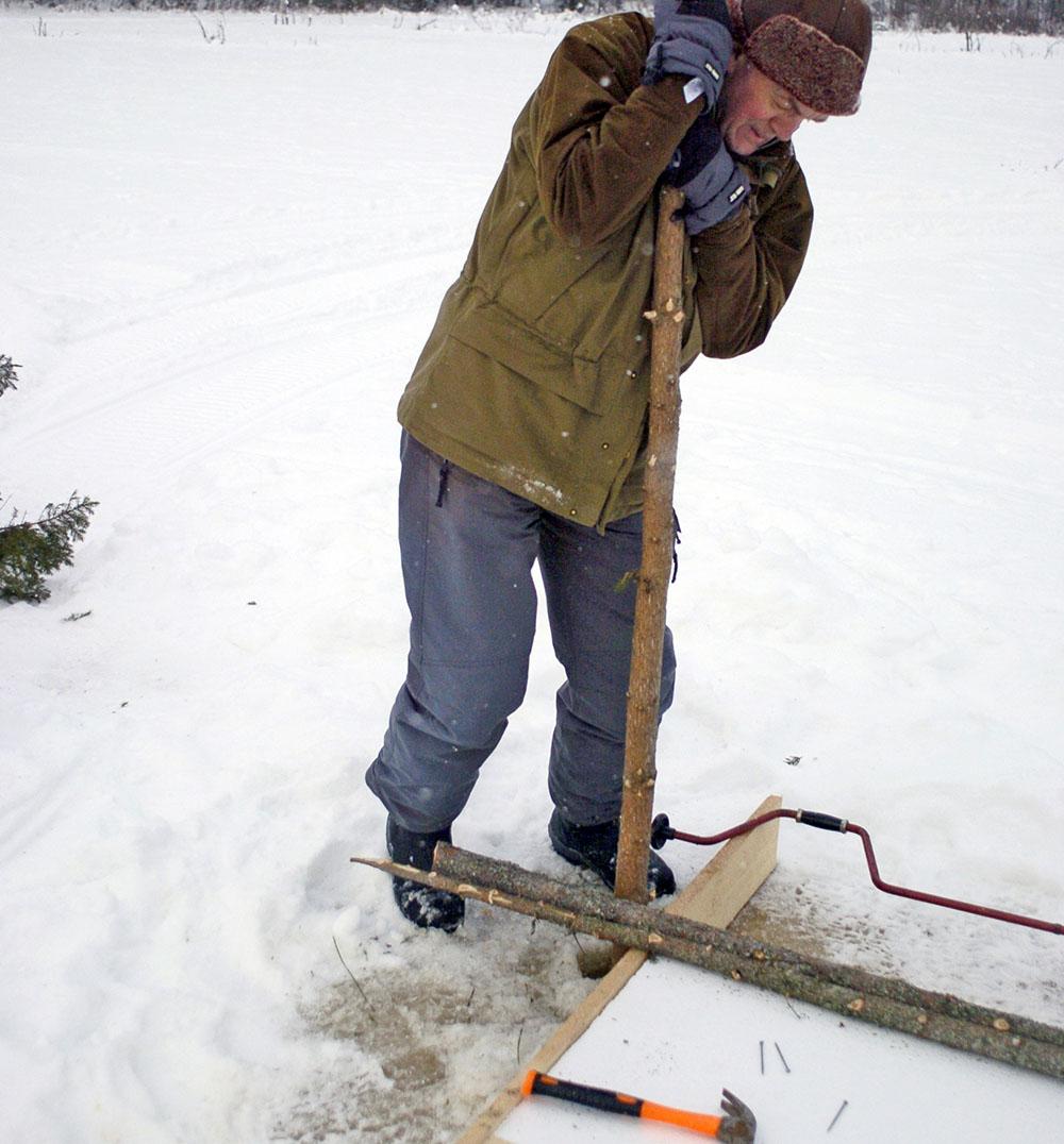 Borra sedan hål i isen med en isborr och driv ner stolpar i de hörn som bildats mellan granslanorna och flottens långreglar.