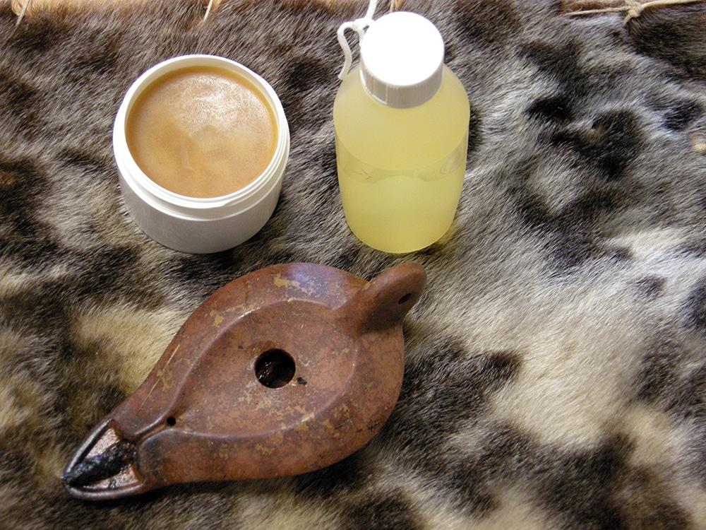 En flaska sälolja, en lampa för sälolja och skosmorning av sälolja. Produkterna som riskerar att inte längre få saluföras står på ett skinn av gråsäl. Foto: Anja Kjellsson